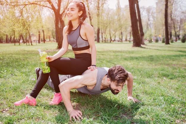Jonge man en vrouw. hij doet push-ups en kijkt recht terwijl ze naar hem zit te lachen.