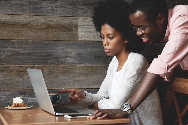 Jonge man en vrouw in café met laptop