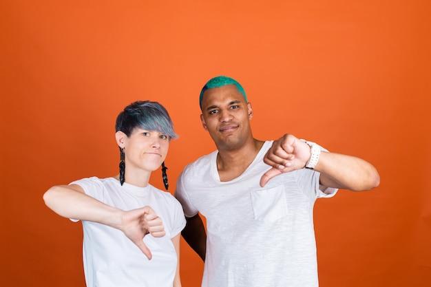 Jonge man en vrouw in casual wit op oranje muur, beide ongelukkig, duim omlaag