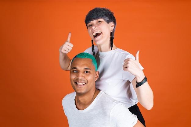 Jonge man en vrouw in casual wit op oranje muur, blije en positieve emoties tonen duim omhoog