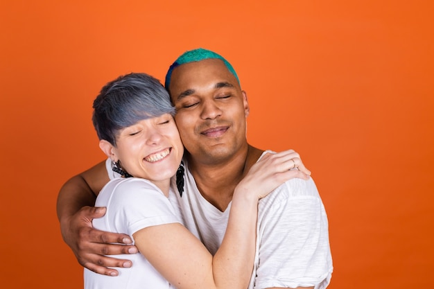 Jonge man en vrouw in casual wit op oranje muur die elkaar stevig omhelzen