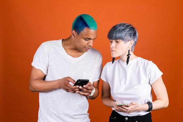 Jonge man en vrouw in casual wit op oranje muur kijken met belangstelling op elkaars telefoonscherm