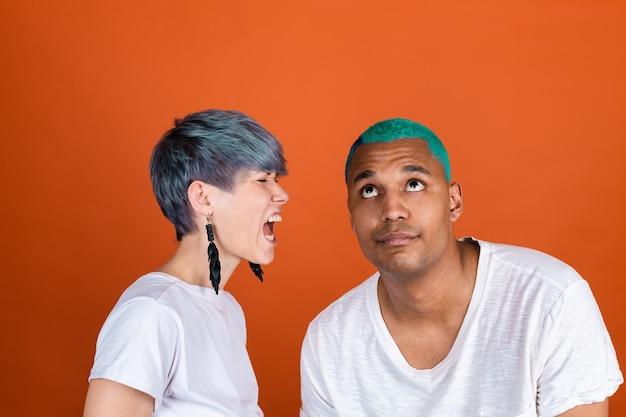 Jonge man en vrouw in casual wit op oranje muur vrouw schreeuwend naar zijn oor, man rolt zijn ogen op moe verveeld geduld