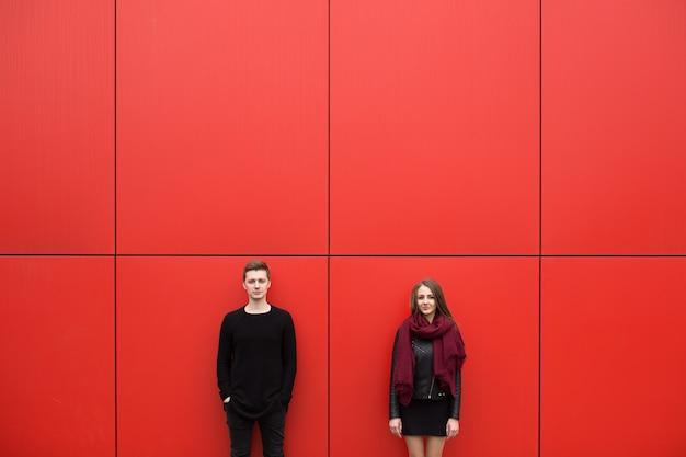 Jonge man en vrouw in hartstocht, emotie, op straat met de rode muur op de achtergrond. mode