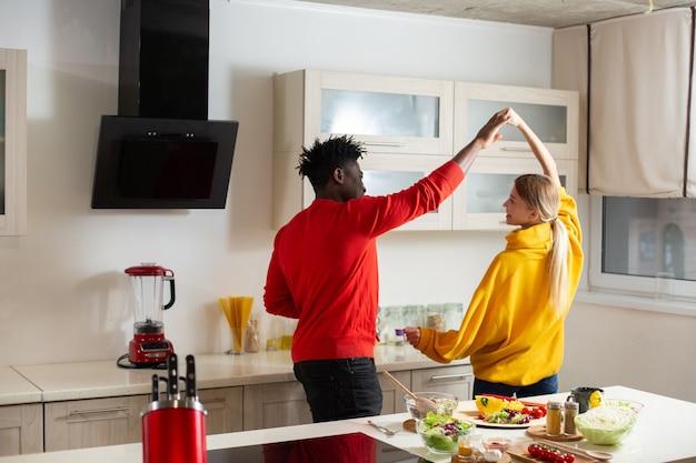 Jonge man en vrouw in kleurrijke truien voelen zich ontspannen en glimlachen terwijl ze elkaars hand vasthouden en dansen in de keuken