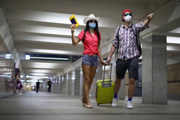 Jonge man en vrouw in medische maskers met koffer en kaartje in hand op luchthaven