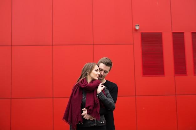 Jonge man en vrouw in passie, emotie, op straat met een achtergrond van de rode muur. mode