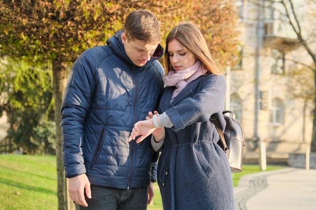 Jonge man en vrouw in stad, kijken naar polshorloge