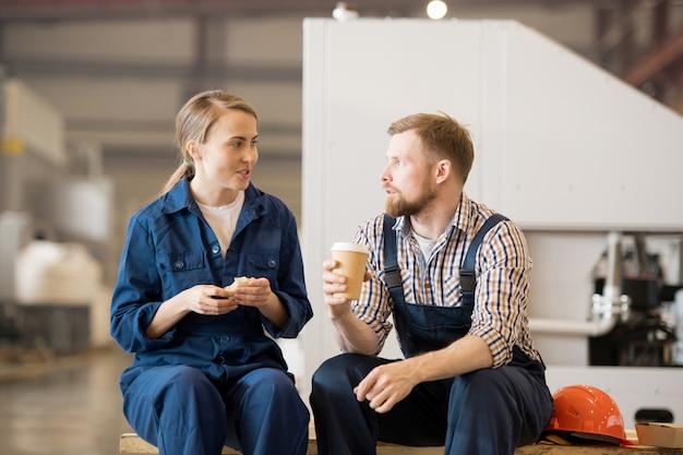 Jonge man en vrouw in werkkleding zitten in werkplaats terwijl het hebben van eten en drinken en praten tijdens pauze
