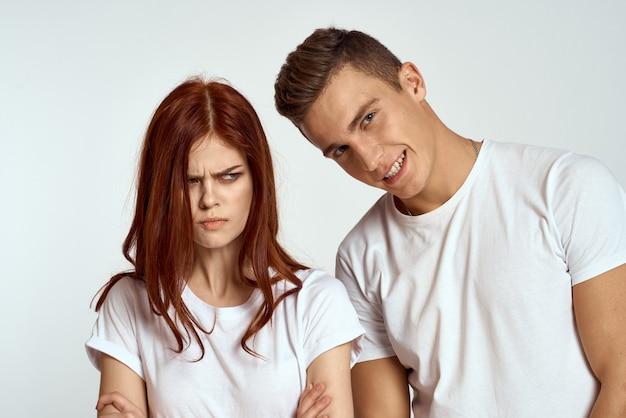 Jonge man en vrouw in witte t-shirts op een lichte muur