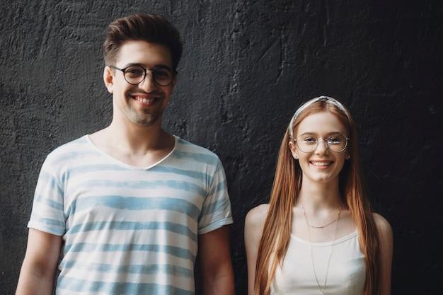 Jonge man en vrouw kijken naar camera tegen een zwarte achtergrond. mooi paar dat buiten dateert. roodharige vrouw met sproeten lachen met haar vriendje.