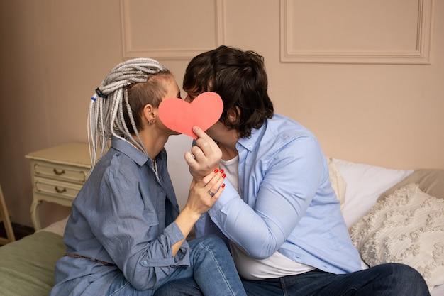 Jonge man en vrouw kussen met rood hart valentijnskaart in handen.