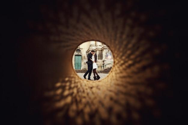Jonge man en vrouw lopen buitenshuis en kussen