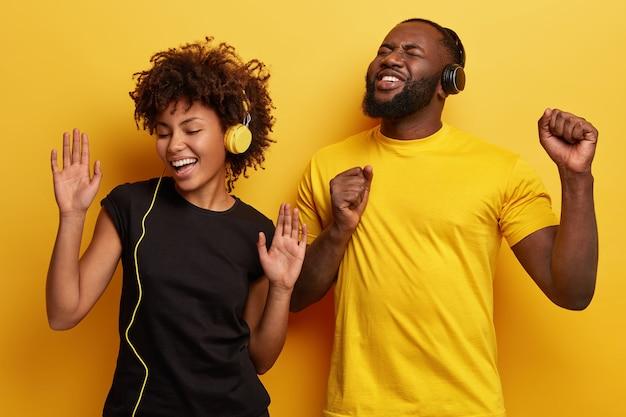 Jonge man en vrouw luisteren naar muziek in de koptelefoon