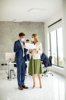 Jonge man en vrouw met beschermende gezichtsmaskers bespreken met papier in handen binnenshuis op kantoor met jonge mensen werkt achter hen