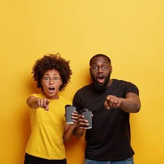 Jonge man en vrouw met kopjes koffie