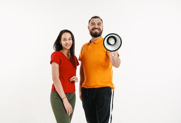 Jonge man en vrouw met levendige t-shirts en megafoon