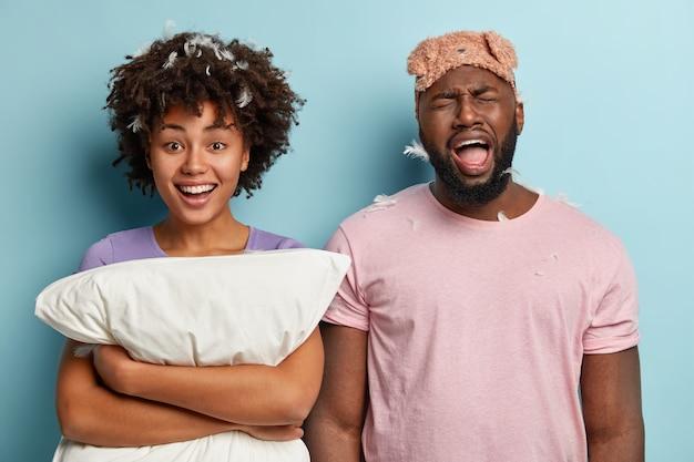 Jonge man en vrouw met slaapmasker en hoofdkussen