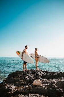 Jonge man en vrouw met surfplanken op steen in de buurt van zee