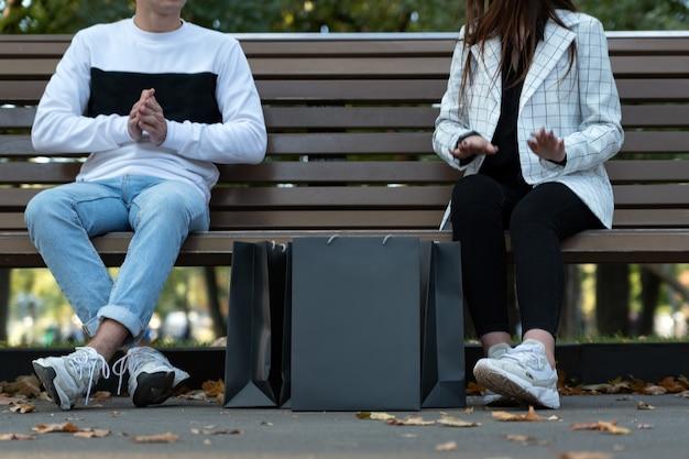 Jonge man en vrouw na succesvol winkelen. zwarte papieren boodschappentassen op de grond. zwarte vrijdag.