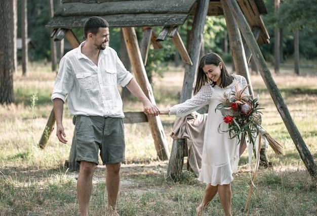 Jonge man en vrouw netjes gekleed, met een boeket exotische bloemen lopen in het bos, op een date in de natuur.