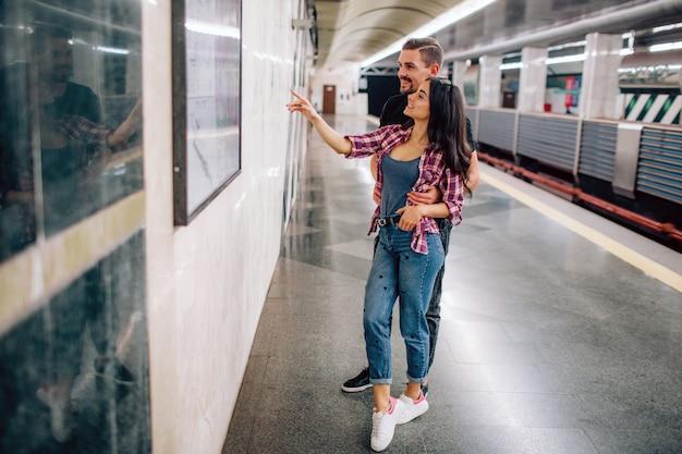 Jonge man en vrouw ondergronds gebruiken. paar in de metro. staand tegen de muur en erop wijzen. vrolijke glimlach. samen op valentijnsdag. casual kleding.