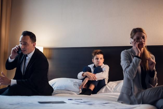 Jonge man en vrouw op hun telefoon, terwijl niemand op hun kind let
