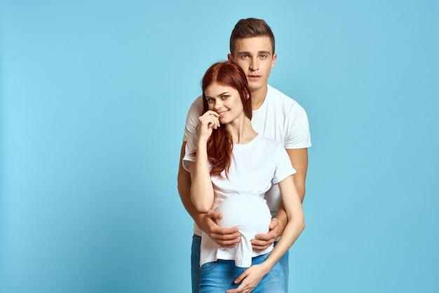 Jonge man en vrouw paar in witte t-shirts op een lichtblauwe muur, zwangere vrouw