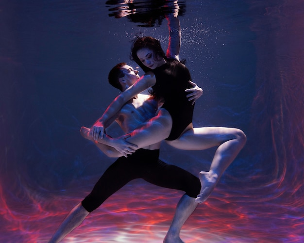 Jonge man en vrouw poseren samen terwijl ze onder water zijn