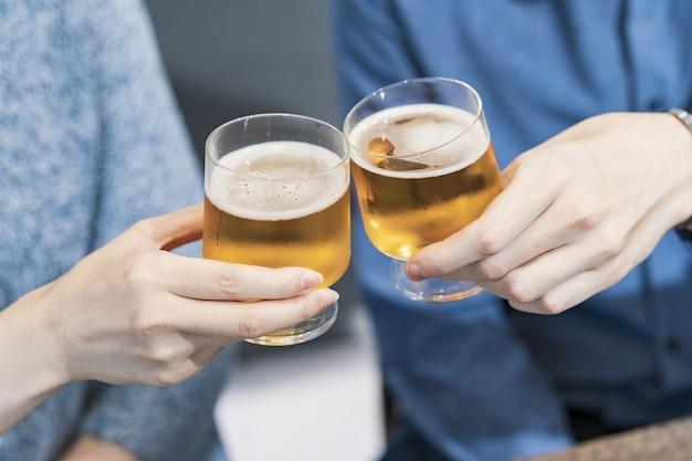 Jonge man en vrouw roosteren met bier