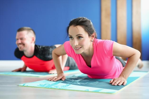 Jonge man en vrouw staan thuis in plank op gymnastiekmatten
