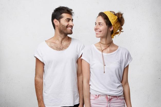 Jonge man en vrouw verliefd hand in hand en kijken naar elkaar