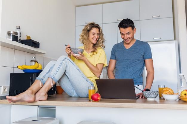 Jonge man en vrouw verliefd met gezond plezier ontbijt in de keuken in de ochtend