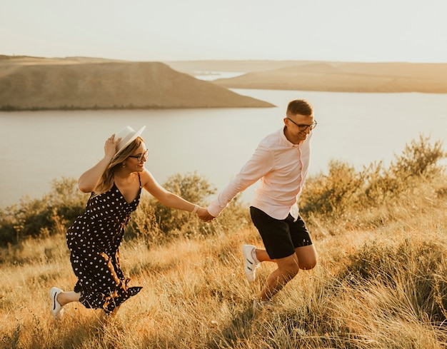 Jonge man en vrouw wandelen in de wei bij zonsondergang in de zomer in de buurt van het meer.