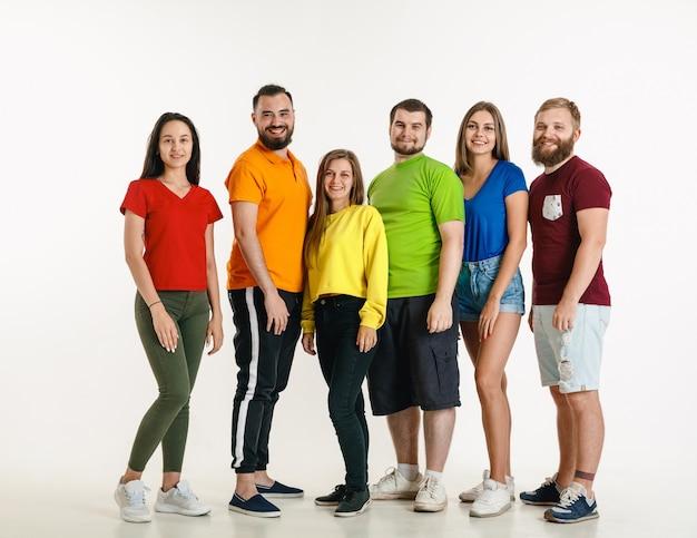 Jonge man en vrouw weared in lgbt-vlagkleuren op witte muur. kaukasische modellen in lichte overhemden. kijk gelukkig, lachend en knuffel. lgbt-trots, mensenrechten en keuzeconcept.