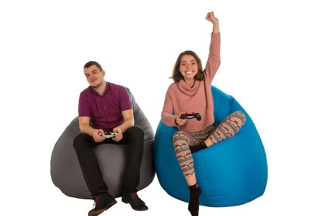 Jonge man en vrouw zijn enthousiast over het spelen van videogames zittend op blauwe en grijze zitzakken voor woonkamer of andere kamer geïsoleerd op wit