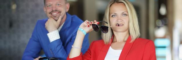Jonge man en vrouw zitten aan de bar met een zonnebril in hun handen