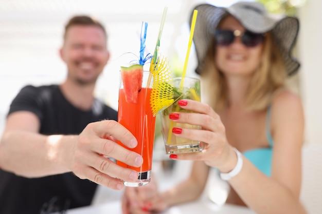 Jonge man en vrouw zitten aan de bartafel en drinken alcoholische cocktails close-up