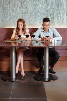Jonge man en vrouw zitten aan de tafel van het restaurant en checken sociale media in plaats van te praten