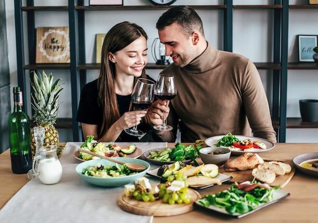 Jonge man en vrouw zitten aan een tafel bedekt met eten en drinken met glazen wijn in hun handen