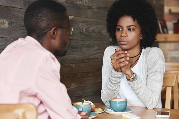 Jonge man en vrouw zitten in café