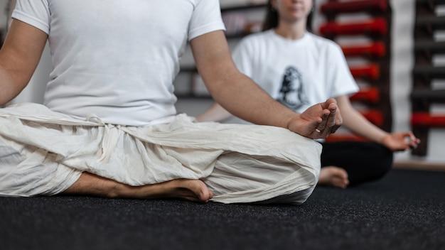 Jonge man en vrouw zitten in lotushouding en mediteert. paar doet yoga. detailopname.