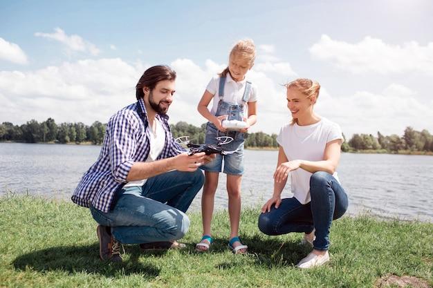 Jonge man en vrouw zitten in squat positie. het kind staat naast hen. guy houdt dronein handen vast. meisje houdt bedieningspaneel. iedereen kijkt naar drone. ze zijn blij en glimlachen.