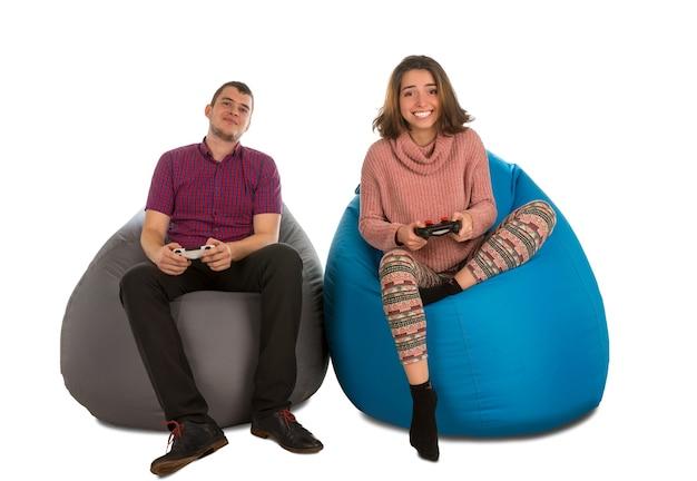 Jonge man en vrouw zittend op blauwe en grijze zitzak stoelen voor woonkamer of andere kamer en spelen van videogames geïsoleerd op wit