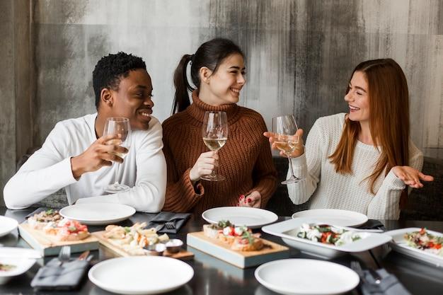 Jonge man en vrouwen die diner hebben samen