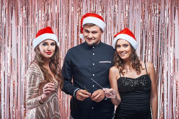Jonge man en vrouwen die van kerstmis met sterretjes in handen genieten.