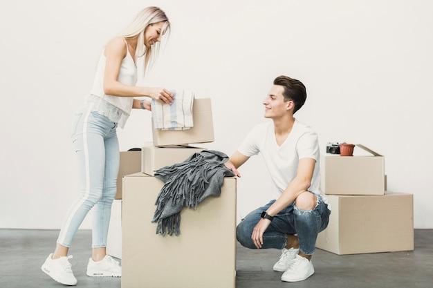 Jonge man en vrouwenverpakkingsdozen
