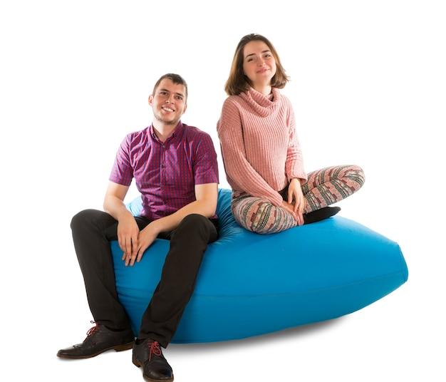Jonge man en vrouwenzitting op blauwe zitzakbank voor woonkamer of andere ruimte die op wit wordt geïsoleerd