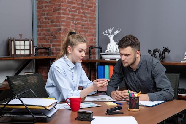 Jonge man en zijn vrouwelijke collega zitten aan tafel en bespreken één probleem in een kantooromgeving