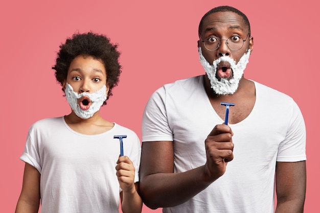 Jonge man en zijn zoon die scheerschuim op gezicht hebben en scheermessen houden